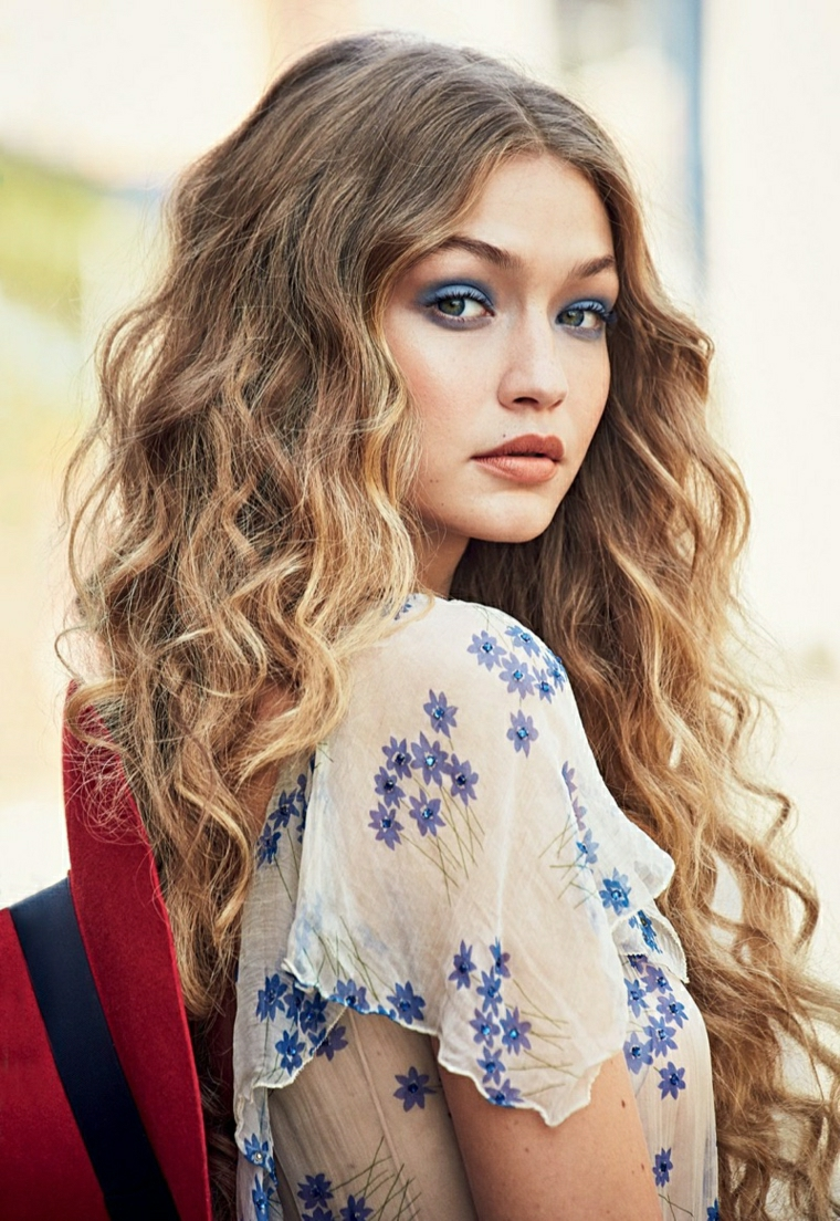 Tagli lunghi e un'idea con una ragazza con i capelli biondi ricci vestita in stile casual