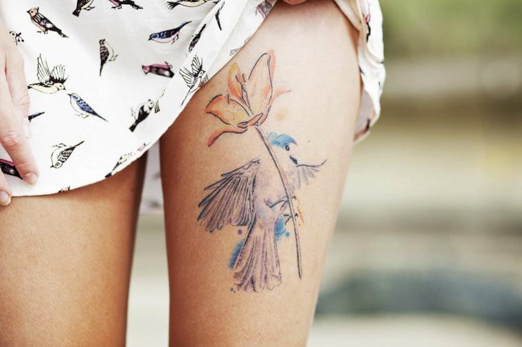 Piccoli tatuaggi, idea per un tattoo femminile da fare sulla gamba. fiore colorato con linee poco definite