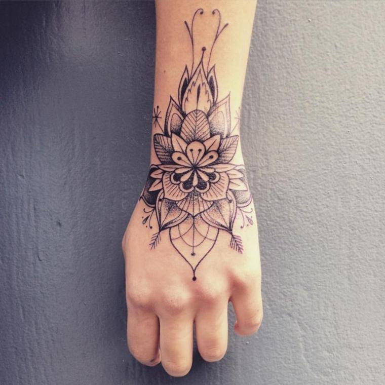 Tattoo piccoli sulla mano, disegno mandala con motivi floreali sul polso di una donna
