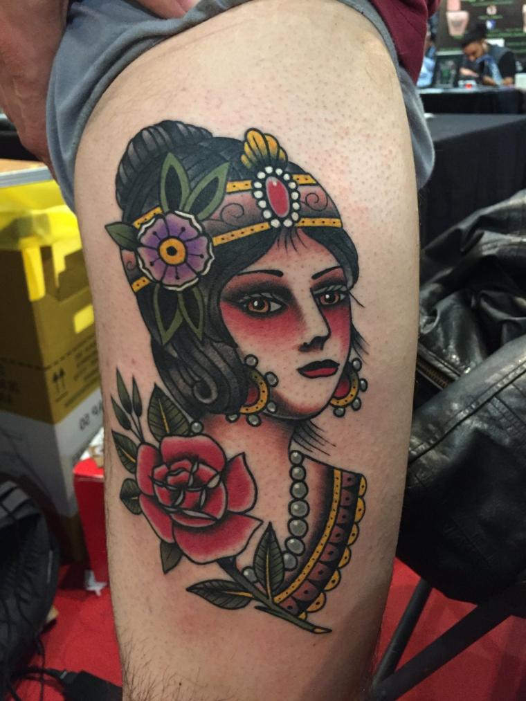 tatuaggio old school, il volto di una donna con orecchini, collana di perle e fiori