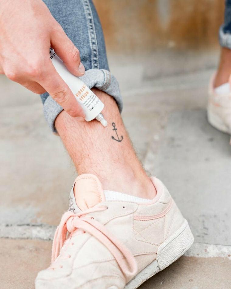 Tatuaggi piede caviglia, tattoo ancora sulla caviglia di un uomo, tubicino con crema per tatuaggi