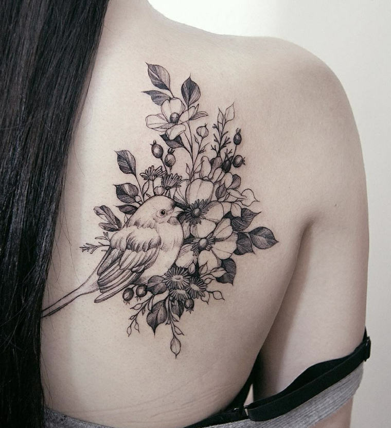 Tatuaggi femminili e un'idea con un uccello e un albero fiorito, colore inchiostro nero con sfumature