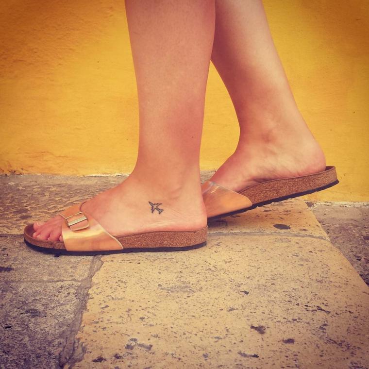 Donna con ciabatte, tatuaggi alla caviglia, disegno tattoo piccolo aereo sulla gamba
