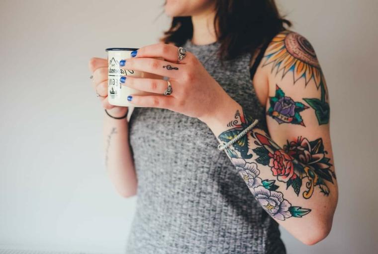 Tattoo colorato sul braccio di una donna, simboli e fiori di vario colore