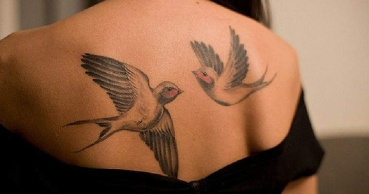 Disegno di due uccelli che volano come tatuaggio sulla schiena di una donna