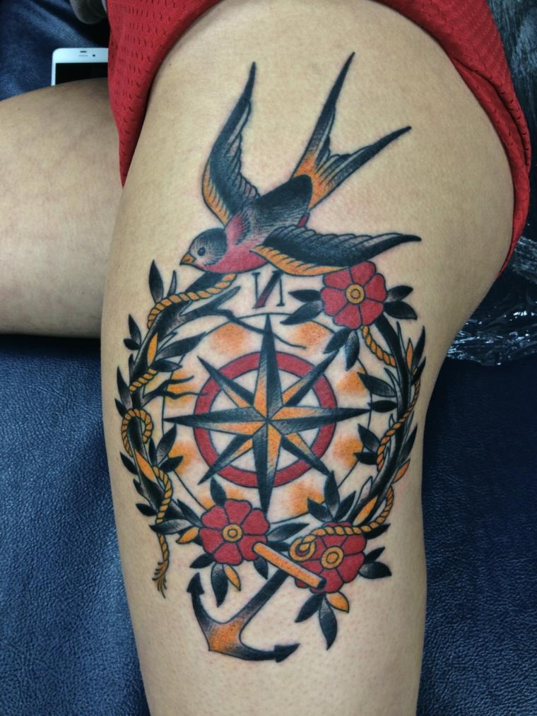 tatuaggi tradizionali, una grande bussola, dei fiori e una rondine colorata