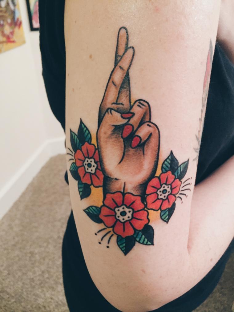 tatuaggi tradizionali, una mano femminile che incrocia le dita e tre fiori rossi