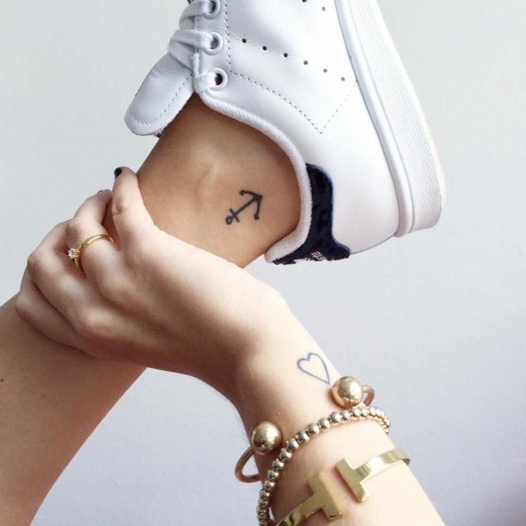 tattoo di dimensioni ridotte, un'ancora tutta nera sulla caviglia e un cuore sul polso