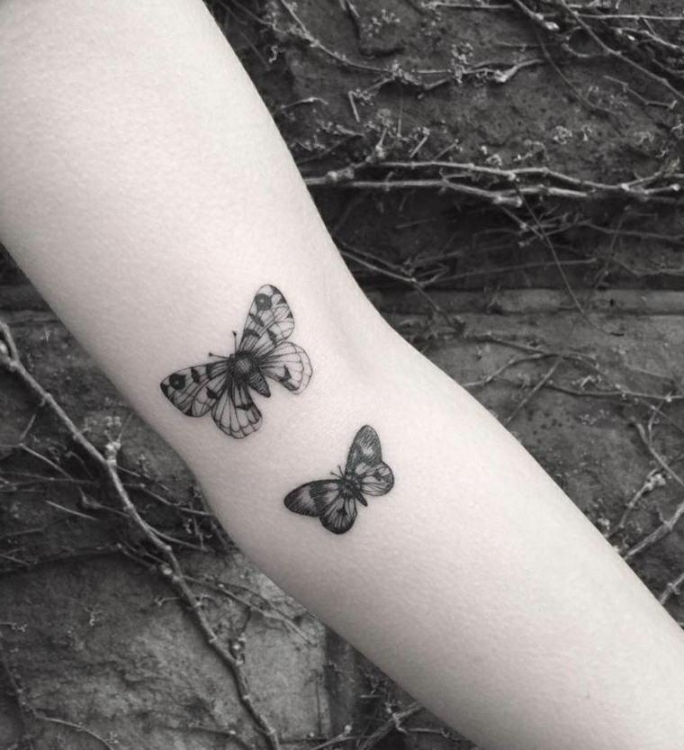 Tatto femminili, idea per due piccoli tatuaggi farfalle di colore nero da fare sul bracci di una donna