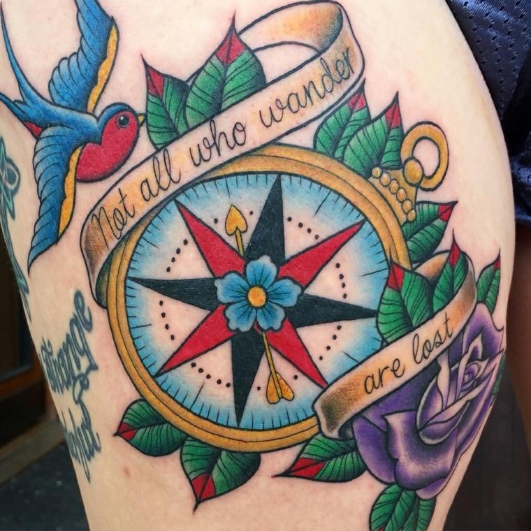 tatuaggi old style, una grande bussola con un fiore al centro, delle scritte e una rondine