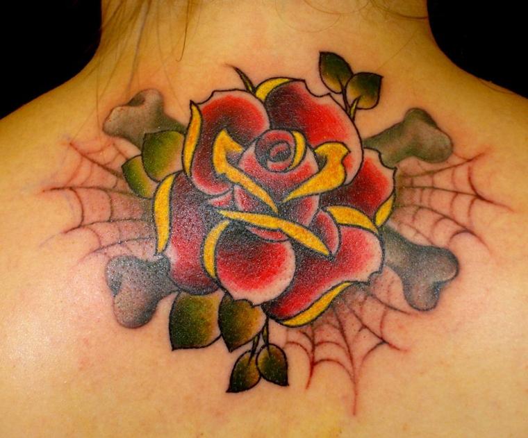 tattoo in stile hold school sulla parte alta della schiena raffigurante una rosa, ossa e una ragnatela