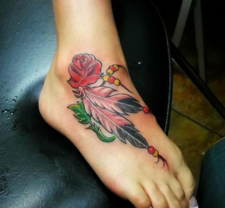 tatuaggio sulla caviglia, che interessa anche il piede con una rosa rossa e delle piume