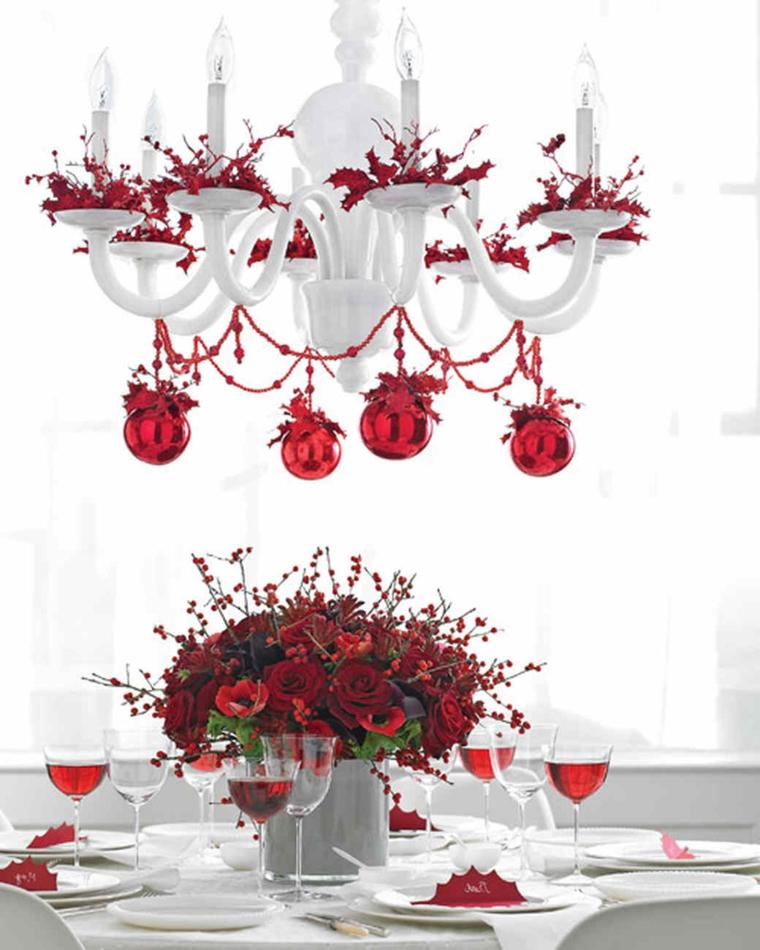 Vaso di porcellana bianca con rose rose e rametti di bacche rosse, lampadario addobbato per Natale