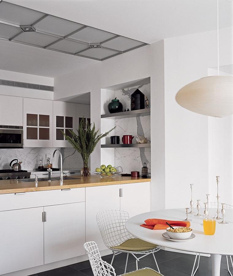 Arredare un open space con mobili di colore bianco, cucina a vista con isola laterale con lavandino