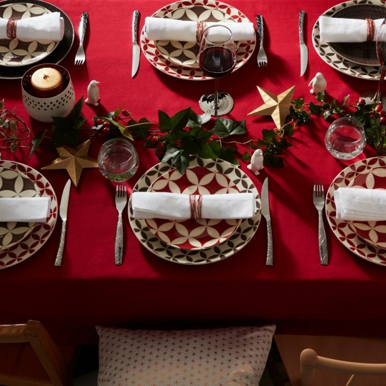 Decorazioni natalizie per il tavolo da pranzo, rametto verde con foglie e stelle dorate come addobbi