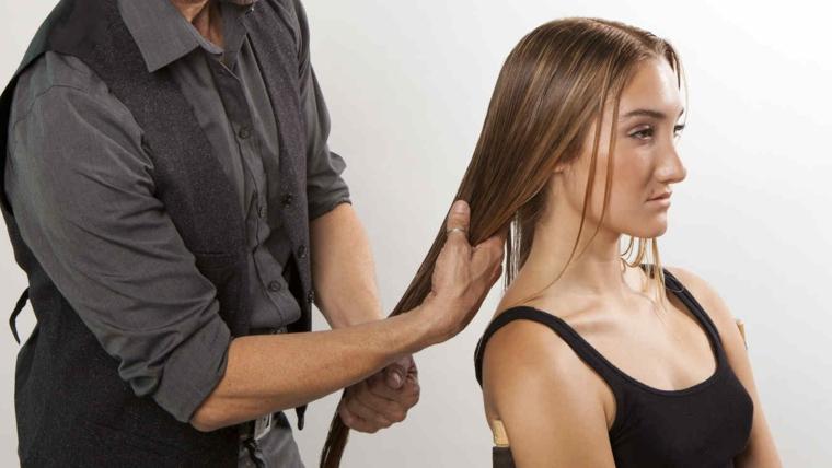 Come trattare i capelli danneggiati, parrucchiere e donna con capelli castano bagnati