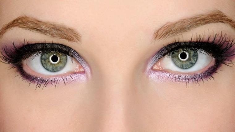 make up per gli occhi verdi realizzato con della matita nera e della matita viola brillante