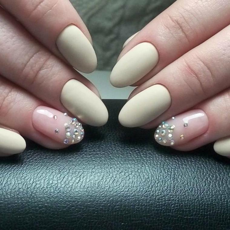 Accent nail di colore rosa chiaro e decorazione con piccoli brillantini, unghie a forma di mandorla di media lunghezza