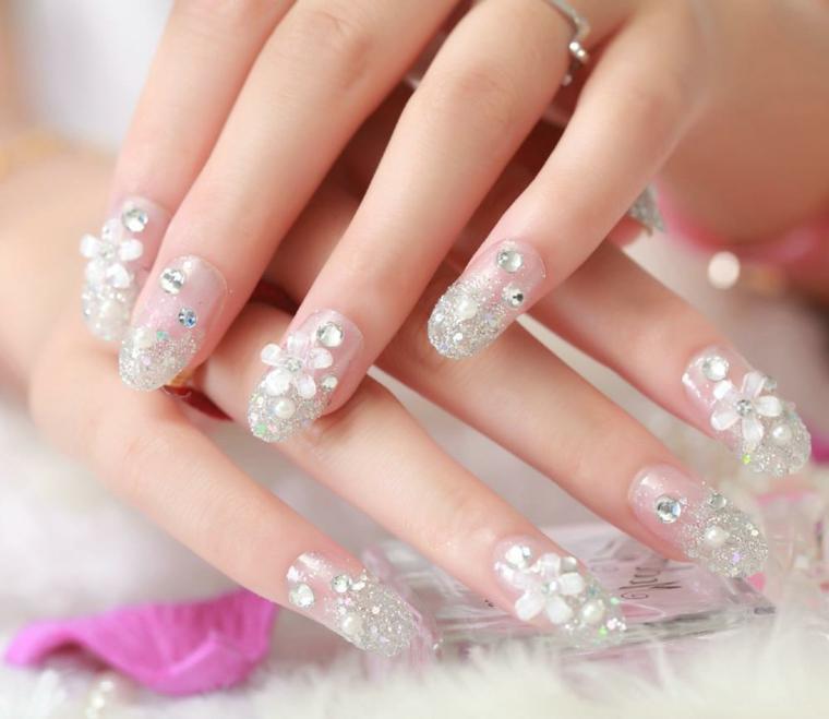 Unghie a stiletto di colore trasparente e decorati con brillantini, decorazione mani in modo elegante