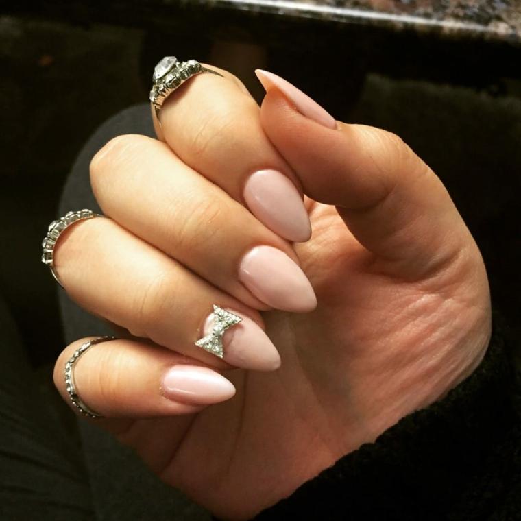 Decorare le unghie a forma di mandorla con un fiocco e brillantino, accessori donna con tanti anelli