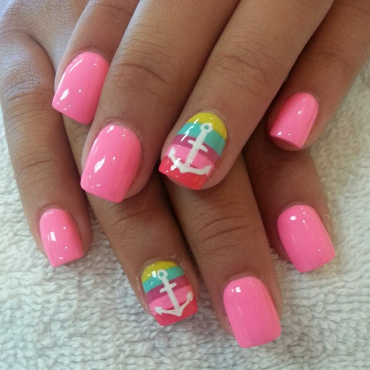manicure giovane ed estiva realizzata con uno smalto di color rosa brillante e l'anulare arcobaleno con un'ancora