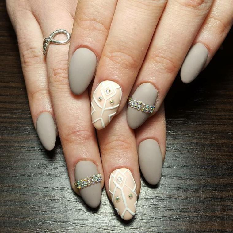 Unghie a mandorla di colore grigio chiaro e beige con accenti decorativi con brillantini, anello infinito in oro bianco