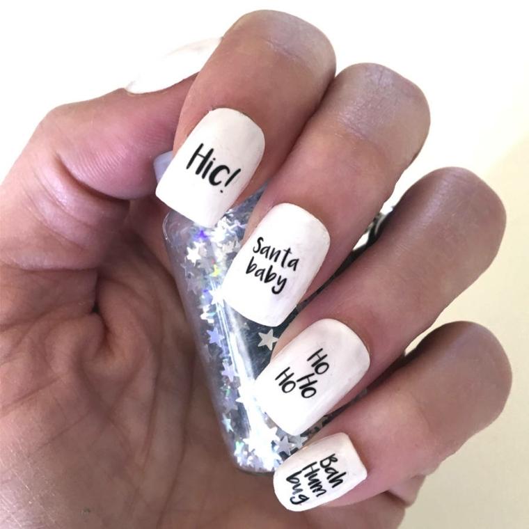 unghie natalizie, una proposta moderna realizzata con dello smalto bianco e delle scritte a tema in nero