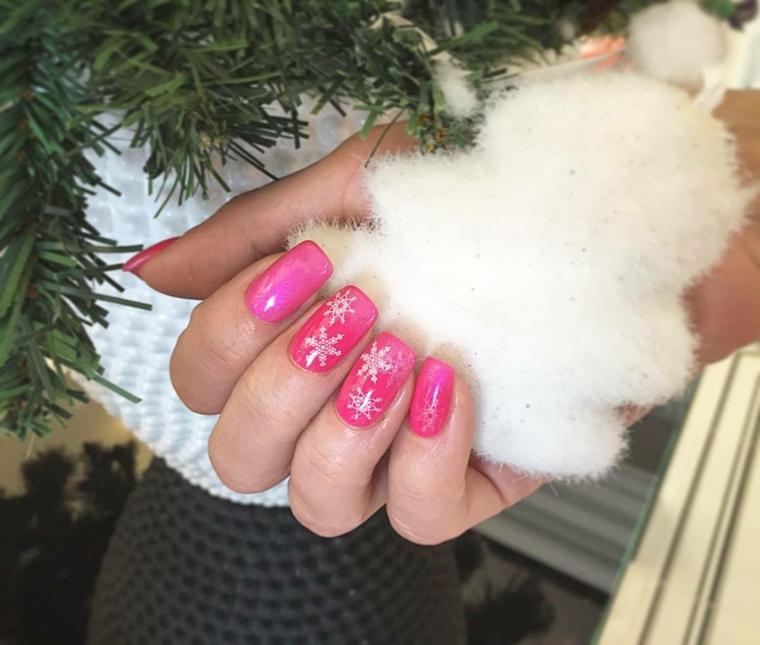 unghie natale, proposta realizzata con dello smalto rosa e delle decorazioni su medio e anulare a forma di fiocco di neve