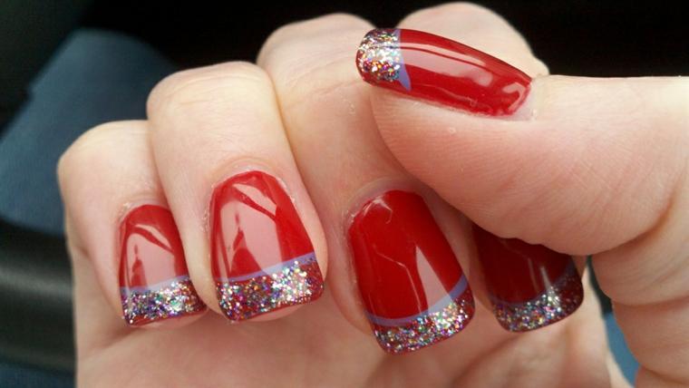 unghie di natale, proposta con uno smalto in gel rosso con una decorazioni nella parte finale con brillantini e riga grigia