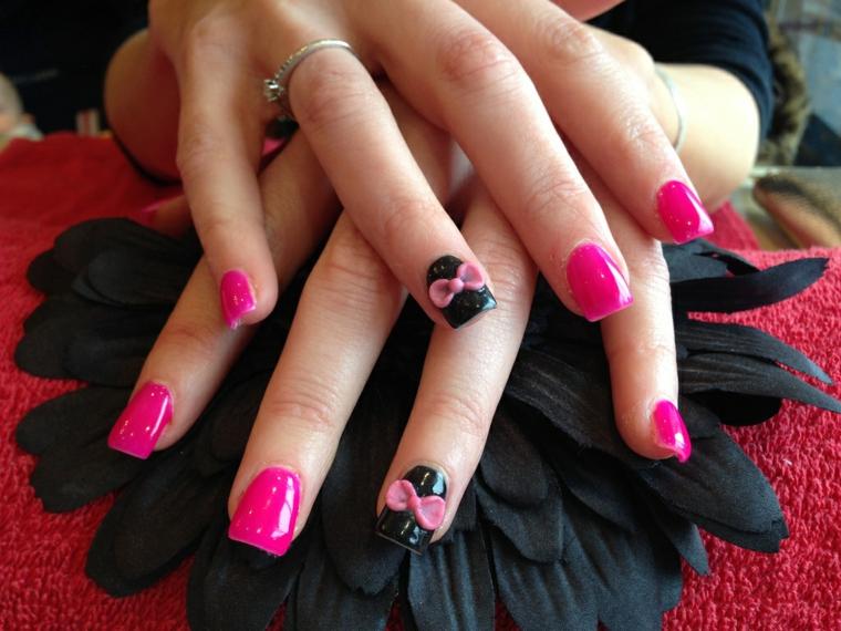 smalto rosa, una manicure realizzata con il gel con l'anulare nero decorato con un fiocco