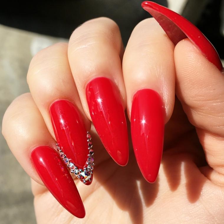 unghie rosse gel, una manicure a stiletto con dei glittert applicati a v sull'anulare