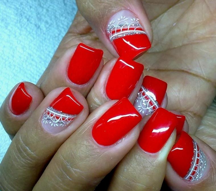 unghie rosso, una manicure realizzata con uno smalto rosso chiaro brillante e decorazioni bianchi e argento