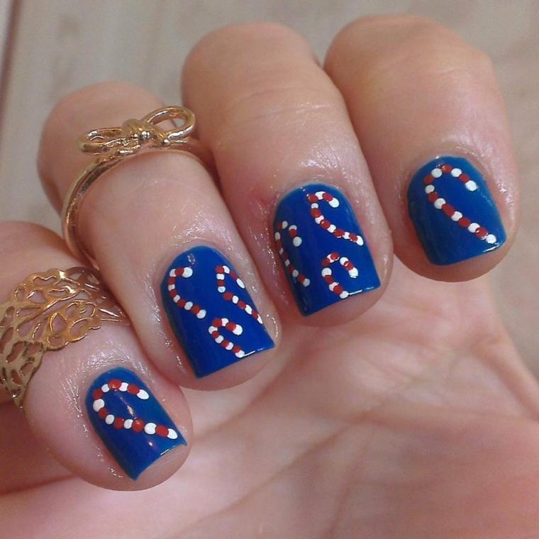 decorazioni a forma di caramelle bianche e rosse su base blu elettrica: idea originale per la manicure delle feste