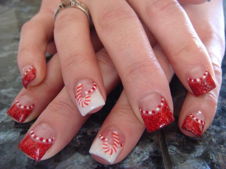 unghia natalizie, una french manicure con lo smalto glitterato rosso e l'anulare bianco con delle decorazioni a forma di caramelle