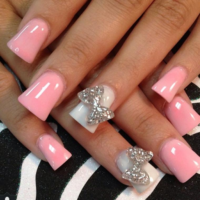 unghie color cipria, una manicure romantica con l'anulare bianco e un fiocco glitterato applicato