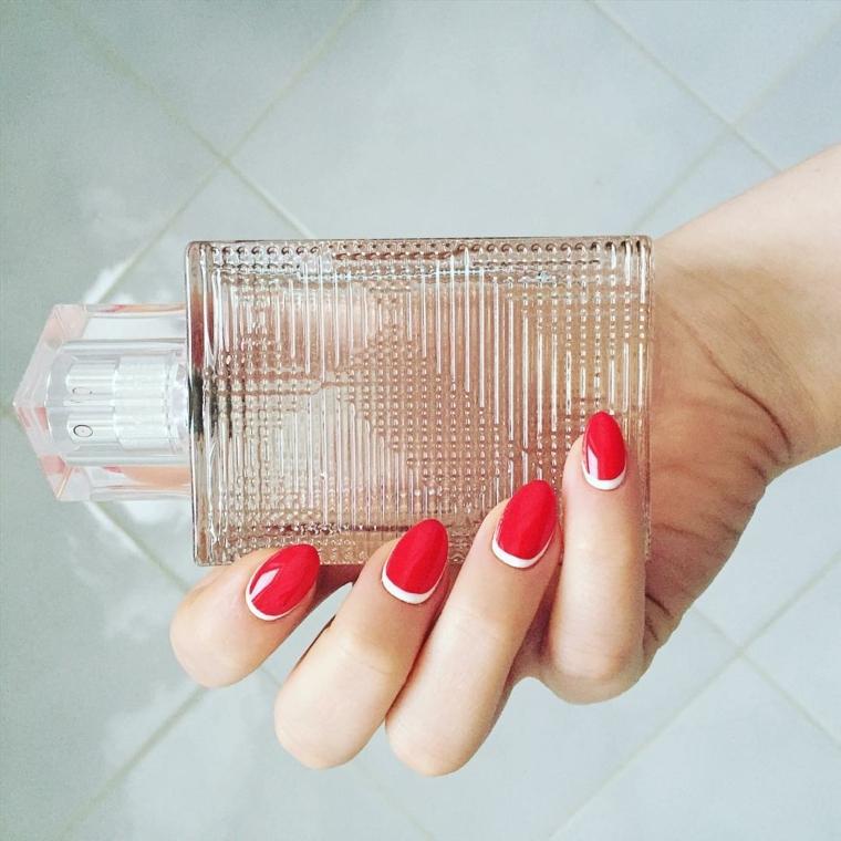 manicure semplice ed elegante con smalto rosso lucido e decorazione bianca intorno alla cuticola