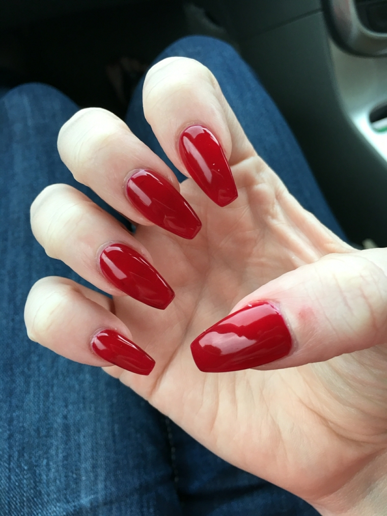 una manicure femminile e sexy realizzata con una tonalità di rosso scura e brillante