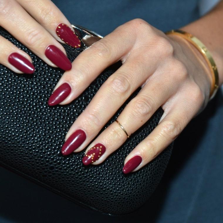 nail art rosso, una manicure giovane e di tendenza con borchiette oro