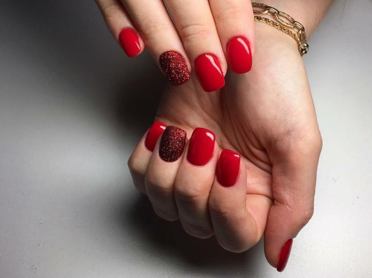 unghie colorate con dello smalto rosso dalla finitura lucida e anulare glitterato