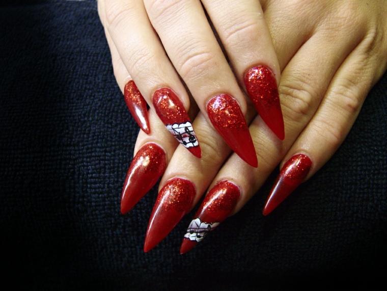 manicure con smalto rosso glitterato e alcune decorazioni bianche e nere sull'anulare