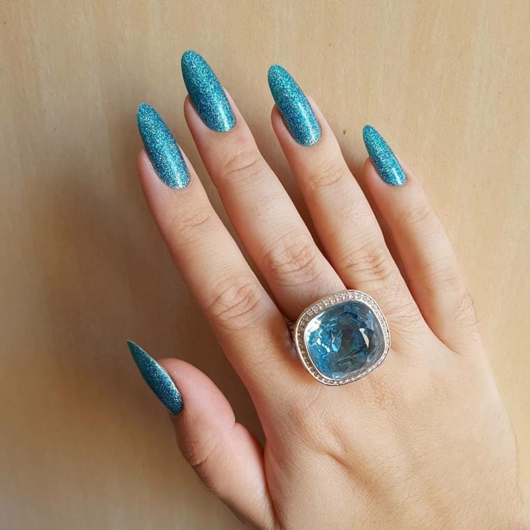 Ricostruzione unghie a mandorla, smalto ruvido di colore azzurro glitterato, accessori donna e un anello con diamante della stessa tonalità di colore