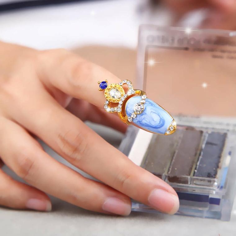 Decorazione di lusso per il dito pollice con uno smalto bianco azzurro e corona in oro con brillantini