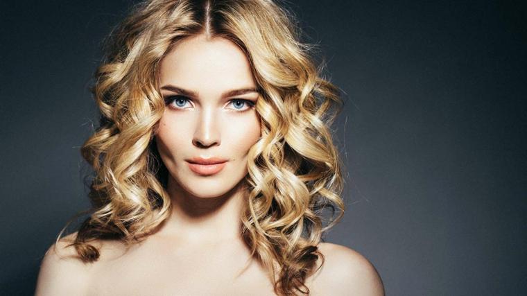 Donna con i capelli di media lunghezza ricci e voluminosi, colore biondo oro