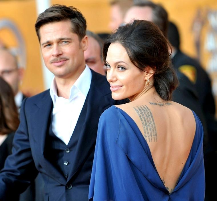 La coppia Brad Pitt e Angelina Jolie, vestito blu con schiena scoperta e tatuaggi in mostra