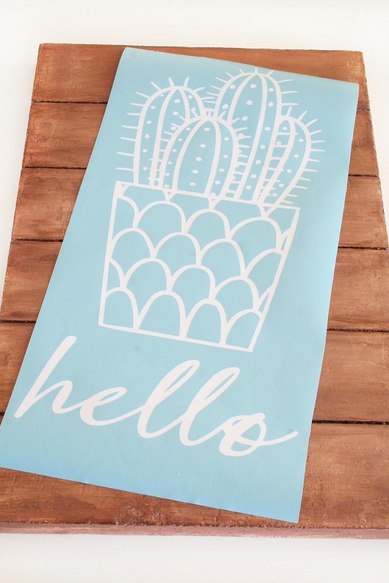Creazioni fai da te e un pannello decorativo in legno decorato con un cactus e scritta Hello