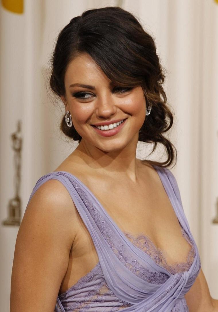 Attrici belle e famose, Mila Kunis con capelli castani e un vestito elegante di colore viola