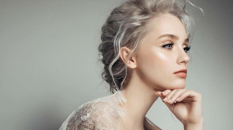 Donna con i capelli legati, lunghi e mossi di colore biondo platino