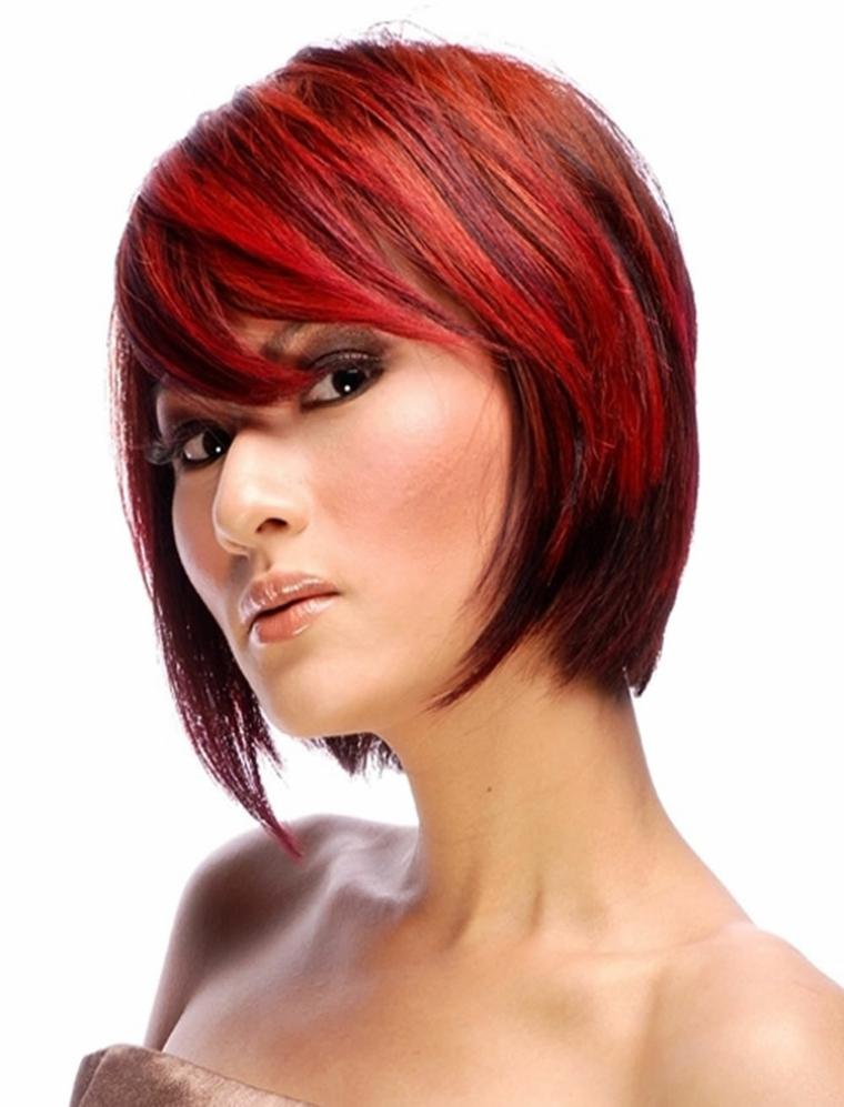 un taglio di capelli scalato con ciuffo a lato e tinta rosso fuoco su base castana