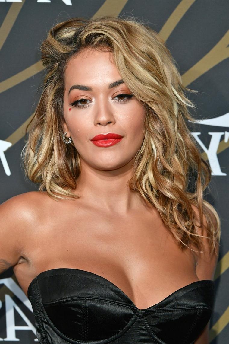 Rita Ora e la sua acconciatura negligé di colore biondo con riflessi, mossi di media lunghezza