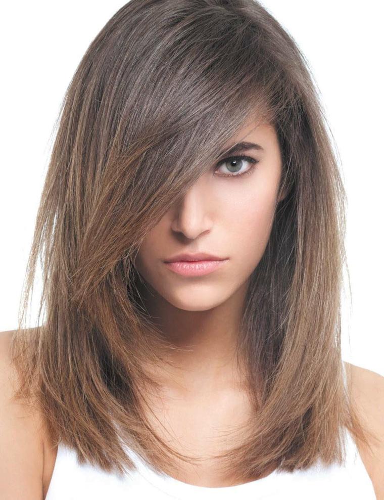 tagli scalati, una proposta per i capelli lisci con ciuffo a lato che copre parte del viso